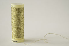 Spule des Goldthreads auf weißem Hintergrund Lizenzfreies Stockbild