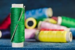 Spule des grünen Fadens mit einer Nadel auf dem Hintergrund von Spulen von farbigen Faden auf einem Denim, Nahaufnahme stockfotos