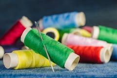 Spule des grünen Fadens mit einer Nadel auf dem Hintergrund von Spulen von farbigen Faden auf einem Denimgewebe stockfoto