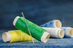 Spule des grünen und gelben Fadens mit einer Nadel auf dem Hintergrund von Spulen des blauen und weißen Fadens auf einem Denim stockfotografie