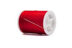 Spule des roten Gewindes und der Nadel auf Weiß Stockbild