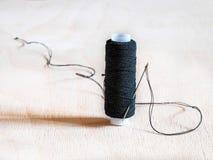 Spule mit schwarzem Thread und mit einer Nadel Stockfotos