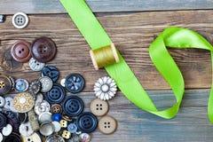 Spule mit Thread, Weinleseknöpfen und grünem Band Stockbild