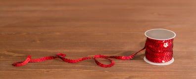 Spule von sequil ribon auf braunem Holztisch Stockfoto