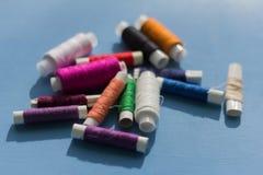 Spulen des farbigen Threads auf einem blauen Hintergrund lizenzfreie stockbilder