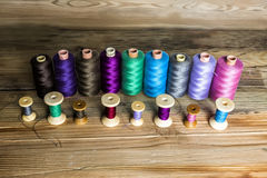 Spulen des Threads auf hölzernem Hintergrund Altes nähendes Zubehör C Stockfotografie