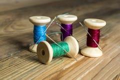 Spulen des Threads mit Nadeln auf hölzernem Hintergrund Altes nähendes a Stockfoto