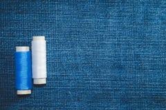 Spulen des weißen und blauen Baumwollfadens auf Jeansgewebe mit Kopienraum lizenzfreies stockfoto