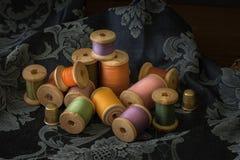 Spulen mit bunten Threads auf altem Holztischhintergrund Stockfoto