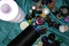 Spulen mit Threads und vielen verschiedenen Knöpfen auf dem Gewebe lizenzfreie stockfotos