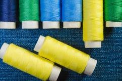 Spulen von gelben, blauen und grünen Faden auf einem Denimgewebe lizenzfreie stockfotos
