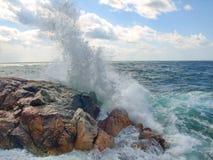 Spuma del mare le spaccature ondeggia contro le rocce nel mare Fotografia Stock