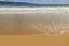 Spuma del mare su una spiaggia sabbiosa Fotografia Stock