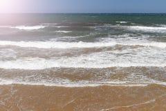 Spuma dell'oceano con acqua del turchese e della spiaggia sabbiosa un giorno di estate soleggiato immagini stock libere da diritti