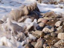 Spuma della schiuma del mare su un Pebble Beach immagini stock libere da diritti