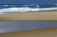 Spuma, spiaggia e raggruppamento di marea Fotografie Stock