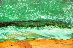 Spuma verde sulle onde dell'alga della sabbia Immagini Stock