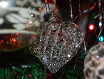 Spun glass heart Christmas tree ornament. Shimmering glass translucent, spun glass heart Christmas tree ornament reflecting red and green lights and silvery royalty free stock photos