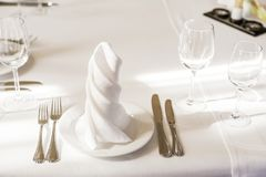 Spun white napkins on a plate on a served table. Plate in a cafe or restaurant with a napkin and appliances. Spun white napkins on a white plate on a served stock photos