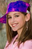 Spunky Little Girl. Fun and spunky head and shoulders portrait of a 12 year old girl wearing makeup and a vivid painter's cap Royalty Free Stock Photo