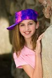Spunky Little Girl. Fun and spunky head and shoulders portrait of a 12 year old girl wearing makeup and a vivid painter's cap peaking around a rock Stock Images