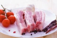 Spuntatura della carne di maiale cruda con le spezie sul piatto Fotografia Stock