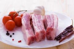 Spuntatura della carne di maiale cruda con le spezie sul piatto Fotografie Stock Libere da Diritti