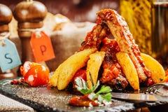 Spuntature della carne di maiale del barbecue con il pomodoro e la patata immagini stock libere da diritti