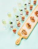 Spuntini, brushettas, colpi di zuppa di verdure fredda, dessert, champagne sopra fondo blu pastello Fotografia Stock