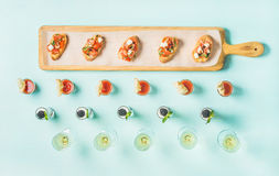 Spuntini, brushettas, colpi di zuppa di verdure fredda, dessert, champagne sopra fondo blu pastello Fotografia Stock Libera da Diritti
