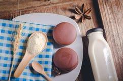 spuntini della torta di choco e bottiglia ricoperti di cioccolato di latte sulla b di legno Fotografie Stock Libere da Diritti
