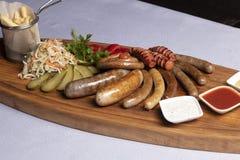 spuntini freddi per birra, le salsiccie ed il formaggio con i pomodori, il prezzemolo e la ciliegia fritti immagine stock