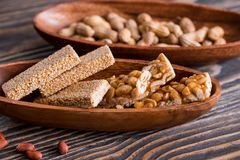 Spuntini - miscela delle barre di energia con i semi dell'arachide, del sesamo e di girasole su un fondo di legno Dadi in caramel fotografia stock libera da diritti