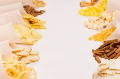 Spuntini variopinti dorati - nacho, popcorn, crostini, chip nel cono della carta del mestiere come rasentano tavola di legno bian Fotografie Stock