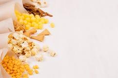 Spuntini variopinti dorati - nacho, popcorn, crostini, chip nel cono della carta del mestiere come rasentano tavola di legno bian Fotografia Stock