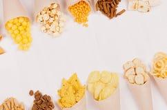 Spuntini variopinti dorati - nacho, popcorn, crostini, chip nel cono della carta del mestiere come rasentano tavola di legno bian Fotografia Stock Libera da Diritti