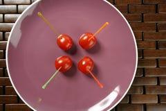 Spuntino dei pomodori in un piatto viola e nei bastoni colorati Immagine Stock