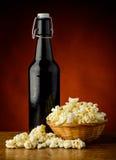 Spuntino del popcorn e della bottiglia di birra Fotografia Stock