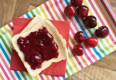 Spuntino della ciliegia Pane tostato con la marmellata di amarene e le ciliege fresche Priorità bassa variopinta Vista superiore Immagini Stock