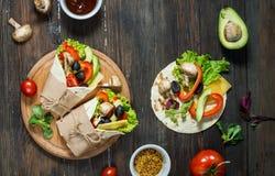 Spuntino sano del pranzo del vegano Involucri della tortiglia con i funghi, gli ortaggi freschi e gli ingredienti su fondo di leg Fotografia Stock Libera da Diritti