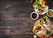 Spuntino sano del pranzo del vegano Involucri della tortiglia con i funghi, gli ortaggi freschi e gli ingredienti su fondo di leg Immagini Stock Libere da Diritti