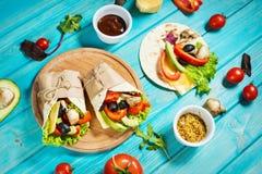 Spuntino sano del pranzo del vegano Involucri della tortiglia con i funghi, gli ortaggi freschi e gli ingredienti su fondo di leg Fotografia Stock