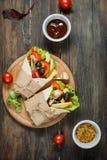 Spuntino sano del pranzo del vegano Involucri della tortiglia con i funghi, ortaggi freschi su fondo di legno Fotografie Stock