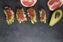 Spuntino sano Ha preparato i sandwihes freschi con l'avocado e pompelmo, formaggio e sesamo nero Vista superiore, spazio vuoto pe fotografia stock libera da diritti