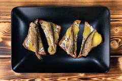 Spuntino: Spratti su pane tostato nero Fotografie Stock