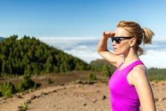 Spur der jungen Frau, die in Berge am sonnigen Sommertag läuft Lizenzfreie Stockfotografie