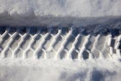 Spur des Autos im Schnee mit Asphalt Lizenzfreies Stockfoto