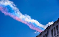 Spur des dreifarbigen Rauches verlassend im Himmel mit den Kampfflugzeugen Su-25 auf Parade zu Ehren des Sieges im Großen patriot Lizenzfreies Stockfoto