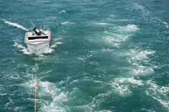 Spur eines Bewegungsbootes mit einem kleinen Boot, das geschleppt wird stockfotos