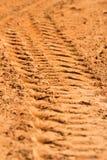 Spur eines Reifens im Sand Stockbilder